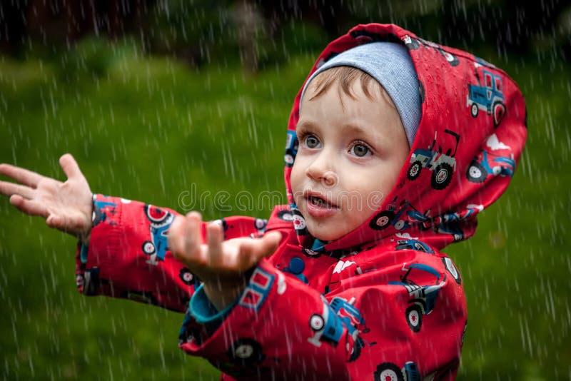 Kleiner Junge in einer wasserdichten Jacke in den Traktoren fangen den Regen Kind, das Spaß draußen in der Sommerdusche hat lizenzfreie stockfotografie