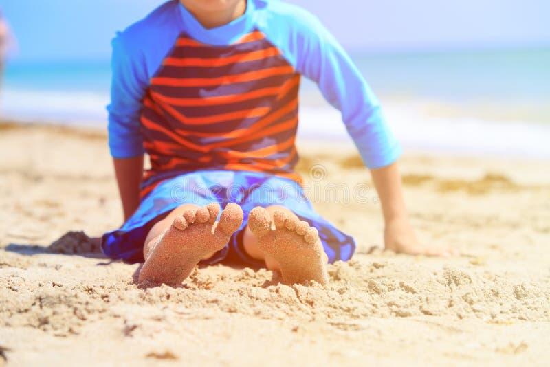Kleiner Junge entspannen sich am Sommerstrand, Fokus auf Füßen stockbilder