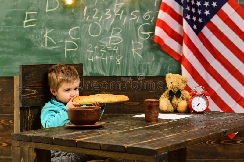 Kleiner Junge essen Brot an der amerikanischen Flagge am Wissenstag Glücklicher Unabhängigkeitstag der USA Zurück zu Schule oder  stockfotografie