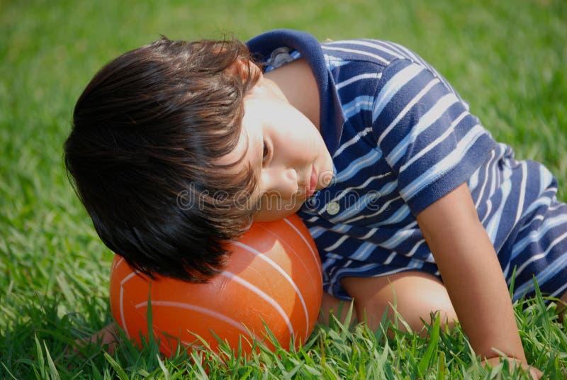 Kleiner Junge ganz heraus tuckered stockfotografie
