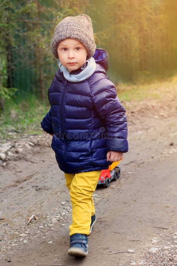 Kleiner Junge geht im Frühjahr auf einen Schotterweg in der warmen Kleidung und trägt die Maschine auf einem Seil stockbild