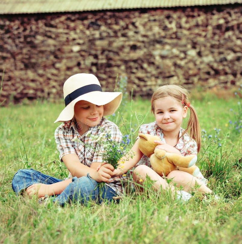 Kleiner Junge gibt dem kleinen Mädchen Blumen stockfotos