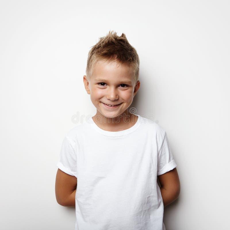 Kleiner Junge hält Hände hinten hinter und an lächelnd lizenzfreies stockbild