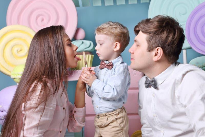 Kleiner Junge hält Lutscher, leckt Mutter ihn und Vater lizenzfreie stockfotografie
