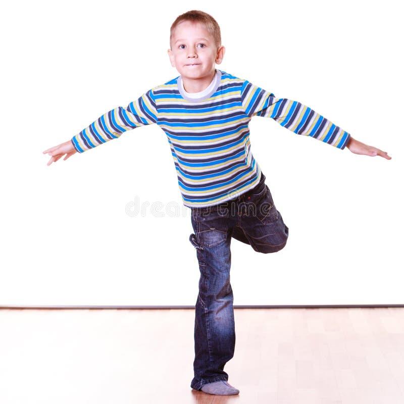 Kleiner Junge haben des Spaßes Stand allein zu Hause auf einem Bein stockfoto