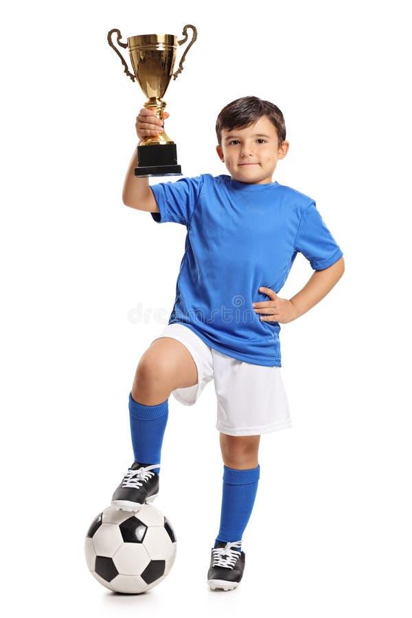 Kleiner Junge im blauen Trikot mit Fußball und Goldtrophäe lizenzfreie stockfotografie
