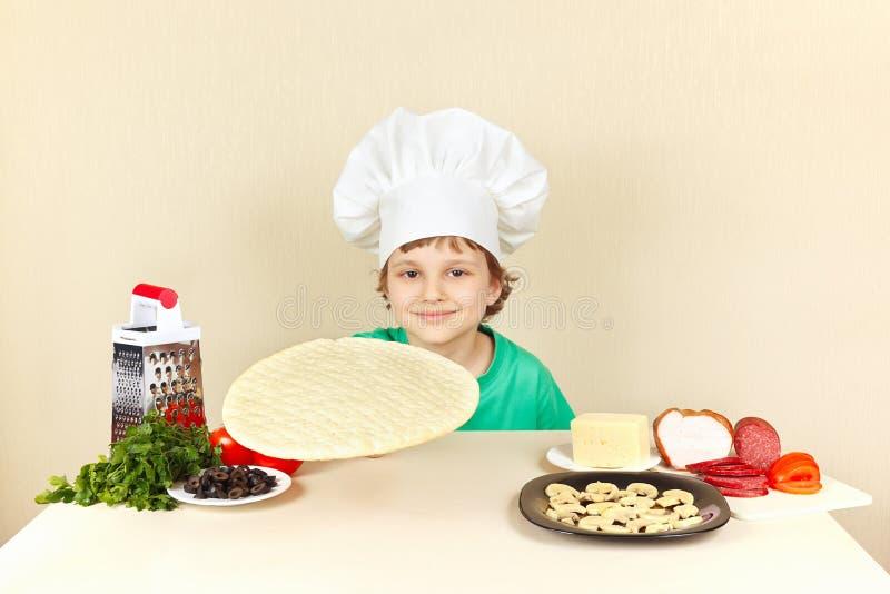 Kleiner Junge im Chefhut am Tisch mit Bestandteilen wird Pizza kochen stockfotografie