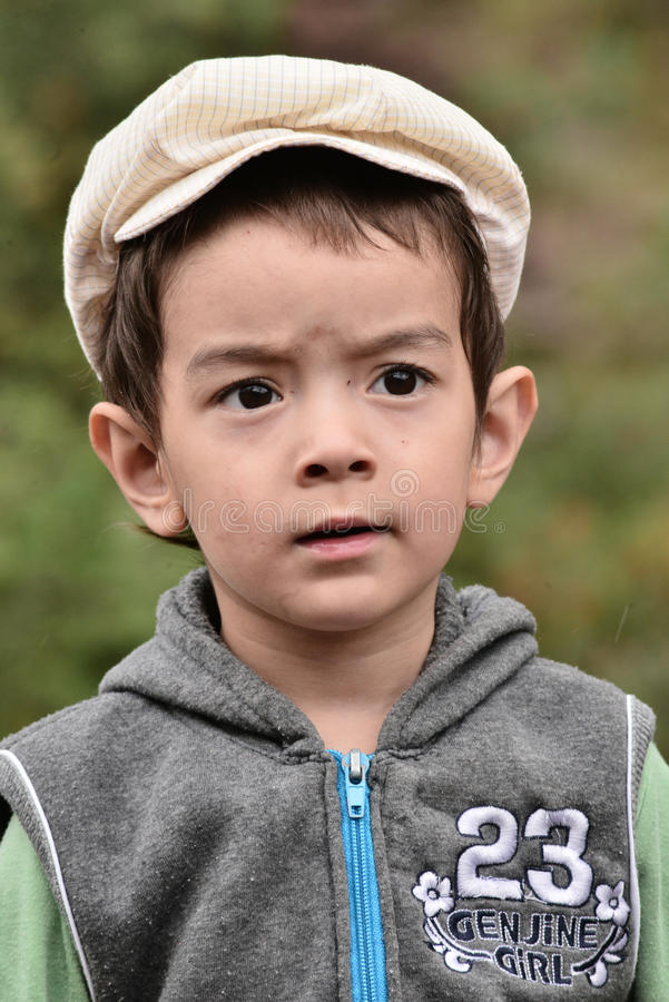 Kleiner Junge im grünen Gras mit einem nachdenklichen Gesicht lizenzfreie stockfotografie