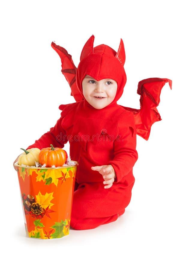 Kleiner Junge im Kostüm des roten Teufels, das nahe großem Eimer sitzt lizenzfreies stockfoto