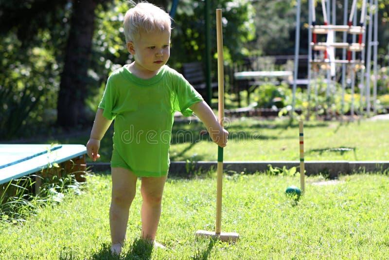 Kleiner Junge im nassen grünen Hemd, das Polo spielt stockfoto