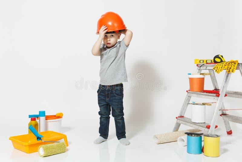 Kleiner Junge im orange Schutzhelm mit Instrumenten für die Erneuerungswohnung lokalisiert auf weißem Hintergrund tapete lizenzfreie stockfotos