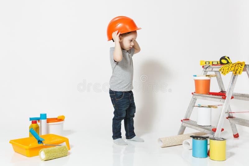 Kleiner Junge im orange Schutzhelm mit Instrumenten für die Erneuerungswohnung lokalisiert auf weißem Hintergrund tapete lizenzfreie stockbilder