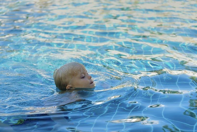 Kleiner Junge im Pool lernt zu schwimmen lizenzfreies stockbild