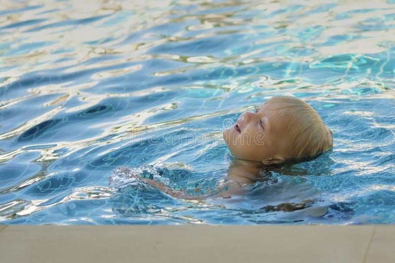 Kleiner Junge im Pool lernt zu schwimmen stockbild