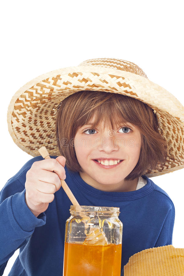 Kleiner Junge isst Honig stockfotos