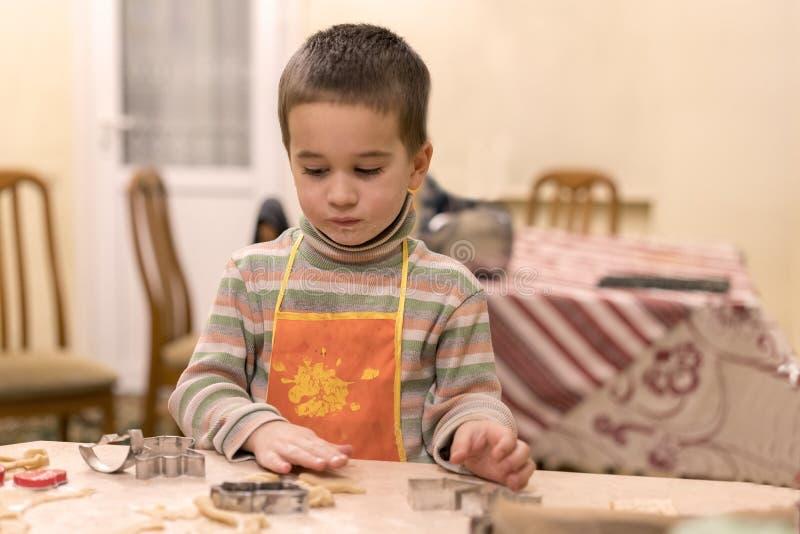 Kleiner Junge 4 Jahre alt in den Plätzchen eines Orangenschutzblechformteil-Teigs stockfotos