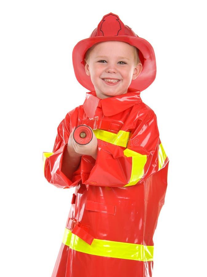 Kleiner Junge kleidete oben als Feuerwehrmann an stockfotografie