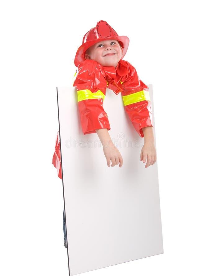 Kleiner Junge kleidete oben als Feuerwehrmann an lizenzfreies stockbild