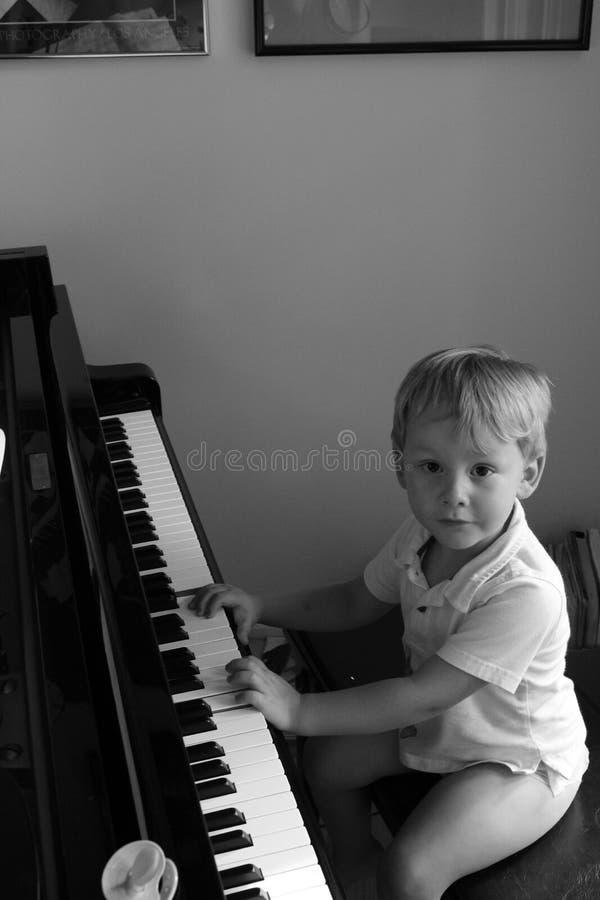 Kleiner Junge am Konzertflügelklavier stockfotos