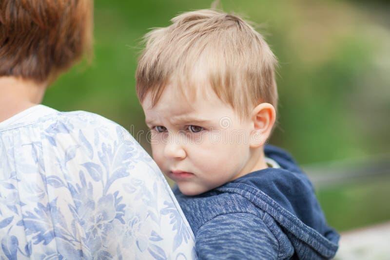 Kleiner Junge lehnt sich an Mutter ` s Schulter und schaut Whiny stockbild