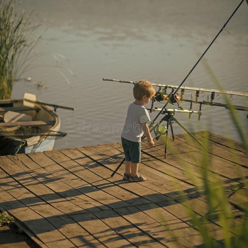 Kleiner Junge lernen, Fische im See oder im Fluss zu fangen lizenzfreie stockfotografie