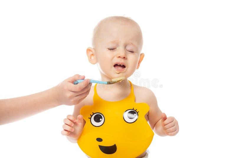 Kleiner Junge möchte nicht essen Säuglingsbaby, das im gelben Schellfisch lokalisiert auf weißem Hintergrund aufwirft Familie, Na stockfotos