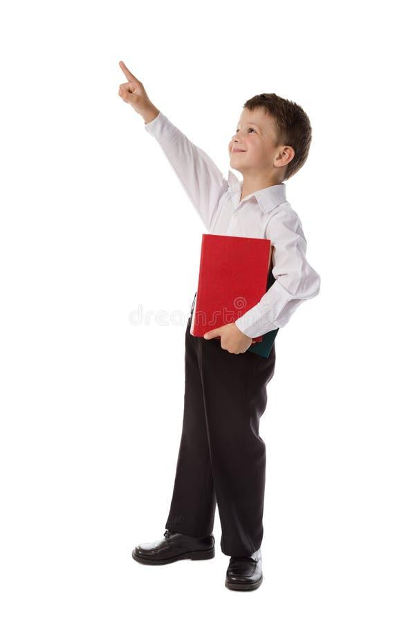 Kleiner Junge mit Buch zeigend bis zum leeren Raum lizenzfreie stockfotografie