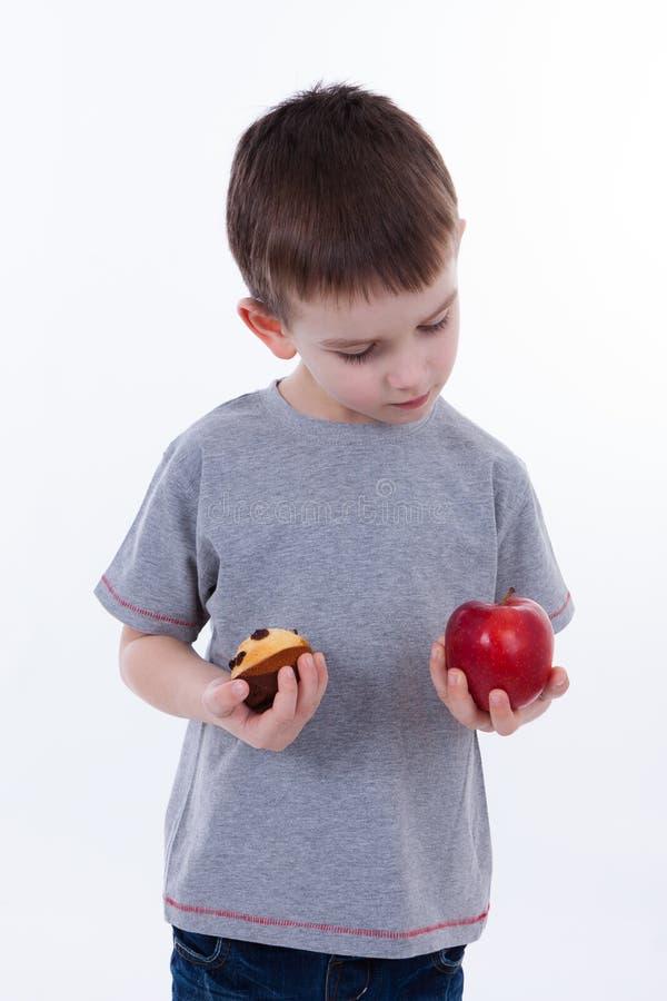 Kleiner Junge mit dem Lebensmittel lokalisiert auf weißem Hintergrund lizenzfreies stockbild