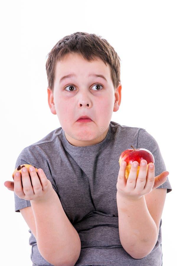 Kleiner Junge mit dem Lebensmittel lokalisiert auf weißem Hintergrund - Apfel oder a.m. stockfoto