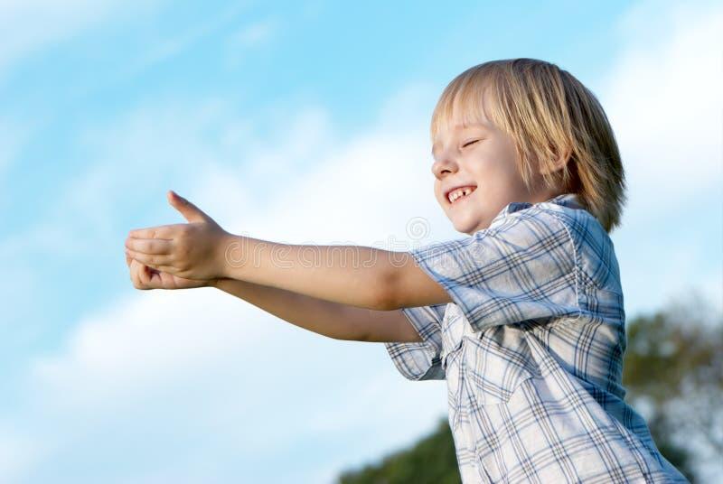 Kleiner Junge mit den ausgedehnten Händen zum Himmel lizenzfreies stockfoto