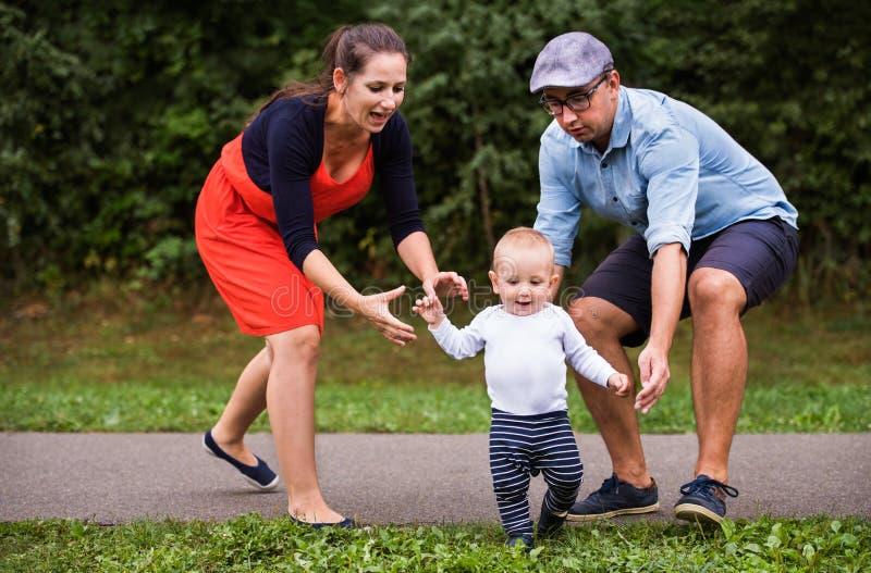 Kleiner Junge mit den Eltern, die erste Schritte machen stockfoto