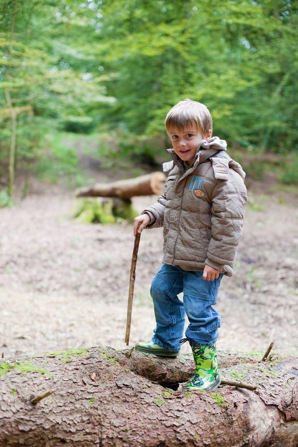 Kleiner Junge mit den Gummistiefeln, die im Holz plaing sind lizenzfreies stockfoto
