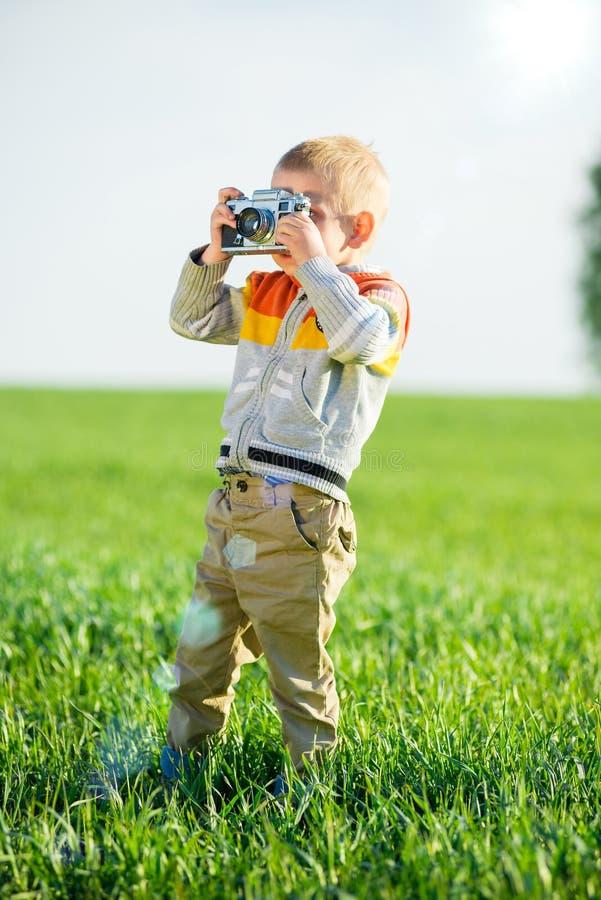 Kleiner Junge mit einem alten Kameraschießen im Freien stockbild