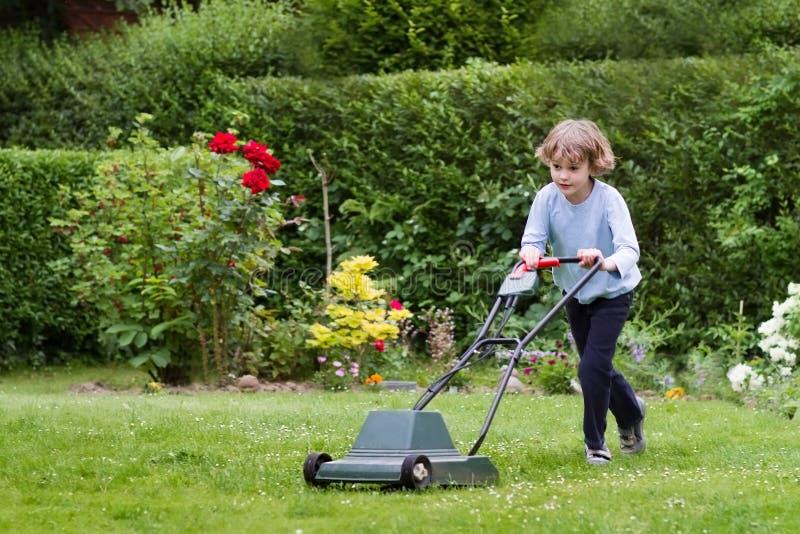 Kleiner Junge mit einem Rasenmäher im Garten stockfotos