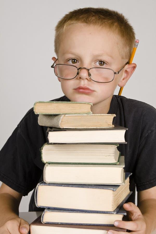 Kleiner Junge mit einem Stapel Büchern lizenzfreie stockfotos