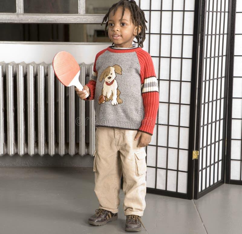 Kleiner Junge mit einem Tischtennishieb lizenzfreie stockfotografie