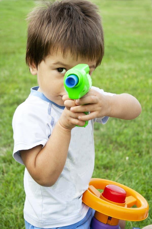 Kleiner Junge mit einer Spielzeuggewehr stockfotos