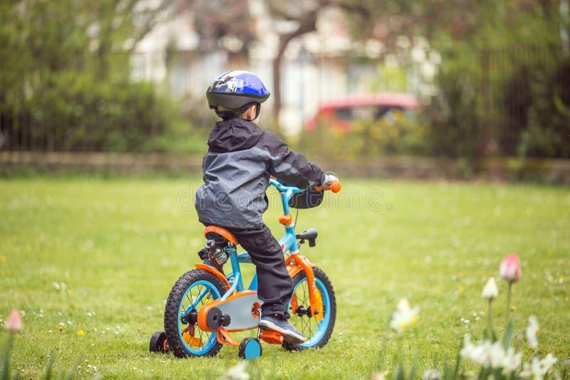 Kleiner Junge mit Fahrrad im Park lizenzfreie stockfotografie