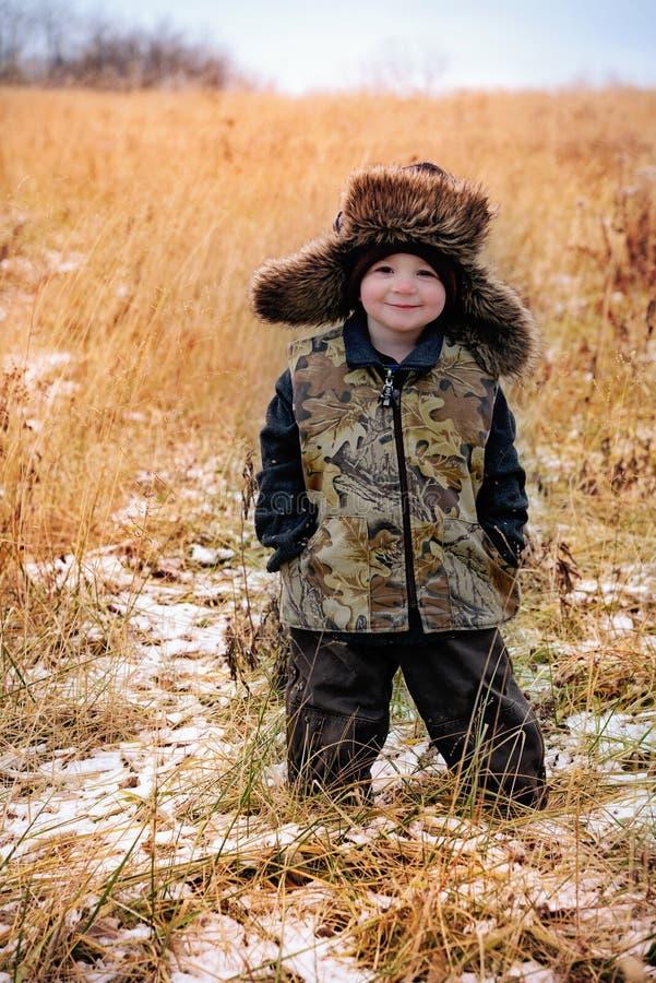 Kleiner Junge mit Faux-Pelztrapper-Hut und Camoweste lizenzfreie stockfotografie