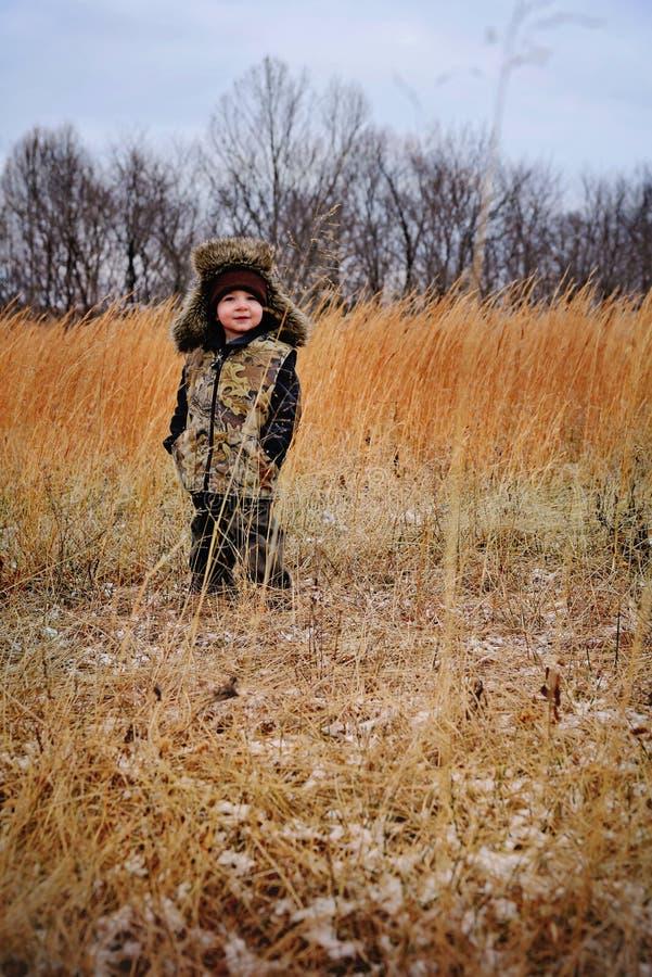 Kleiner Junge mit Faux-Pelztrapper-Hut und Camoweste lizenzfreie stockbilder