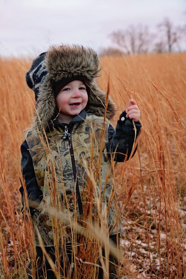 Kleiner Junge mit Faux-Pelztrapper-Hut und Camoweste lizenzfreie stockfotos