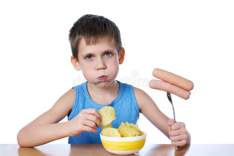 Kleiner Junge mit fetten Backen Wurst- und Kartoffelchipisolator essend stockfoto