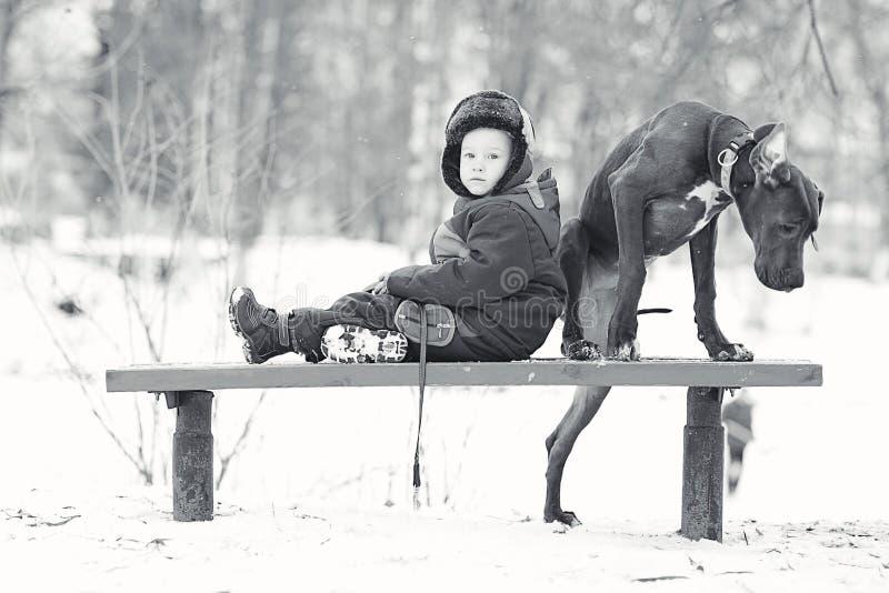 Kleiner Junge mit großer schwarzer Hunderasse stockfotografie