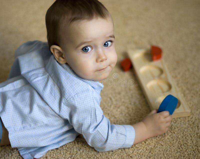 Kleiner Junge mit intellektuellem Spielzeug lizenzfreie stockbilder