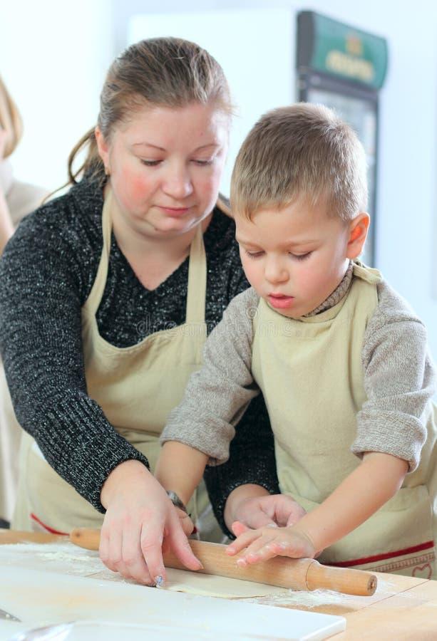 Kleiner Junge mit seinem Mutterkochen stockfoto