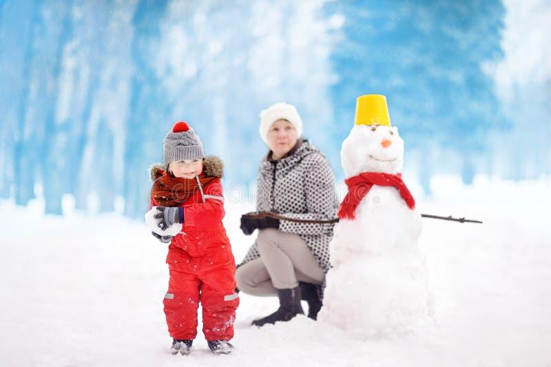 Kleiner Junge mit seiner Mutter/Babysitter/Großmutter, die Schneeballkampf im schneebedeckten Park spielt stockbild