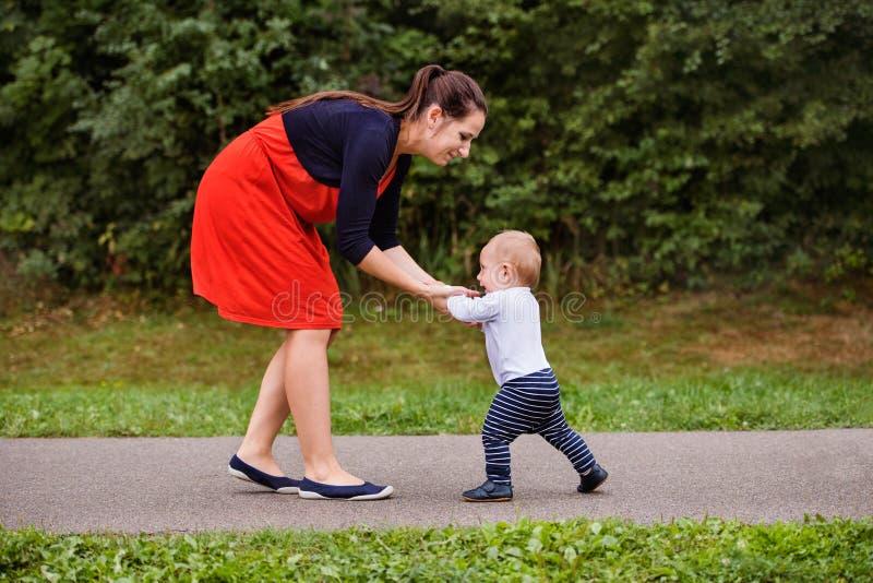 Kleiner Junge mit seiner Mutter, die erste Schritte macht stockfoto