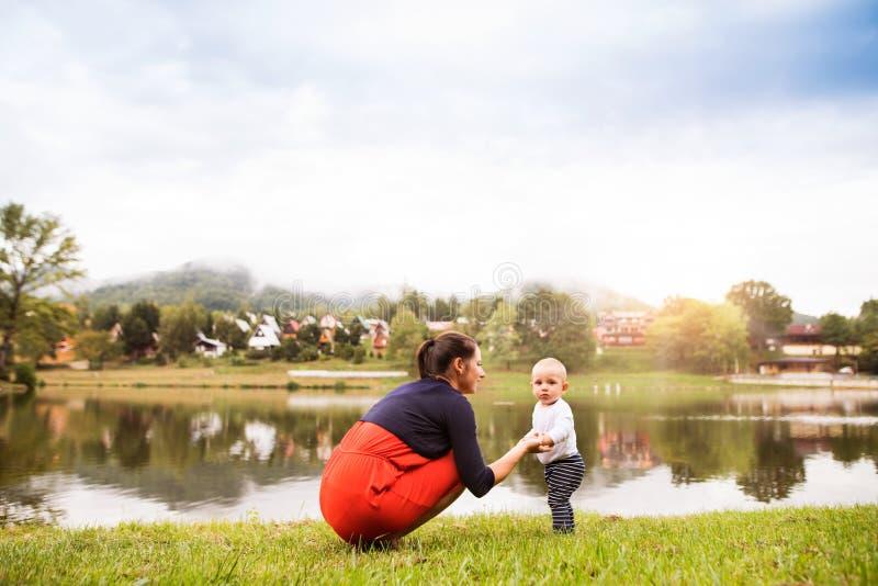 Kleiner Junge mit seiner Mutter, die erste Schritte macht lizenzfreie stockbilder