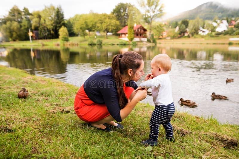 Kleiner Junge mit seiner Mutter, die erste Schritte macht lizenzfreies stockbild