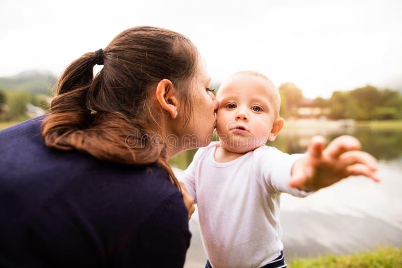 Kleiner Junge mit seiner Mutter, die erste Schritte macht lizenzfreie stockfotos